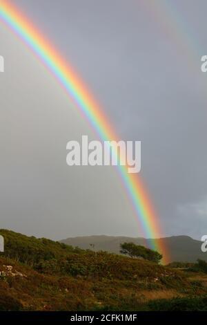 Un arco iris sobre Duirinish y Plockton en una noche tormentosa, West Highlands, Escocia, Reino Unido.