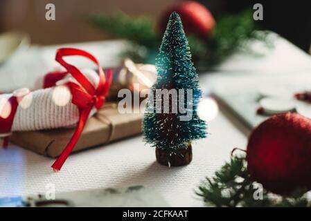 Pequeño juguete verde abeto colocado cerca de regalo de Navidad envuelto en papel artesanal sobre la mesa con decoraciones en contra de brillo borroso garland