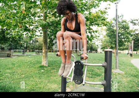 Bajo ángulo de positivo joven pelo rizado negro deportista haciendo empuje en los bares paralelos en el parque de verano