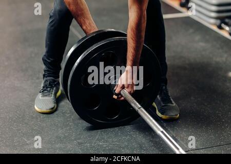 Cosecha atleta masculino anónimo en sportswear poner placas pesadas barbell mientras se prepara para el entrenamiento de pesas en el gimnasio