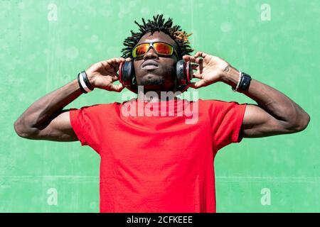 Atleta afroamericano masculino en ropa deportiva y con auriculares relajante en la calle después de entrenar en el día soleado mientras se está mirando