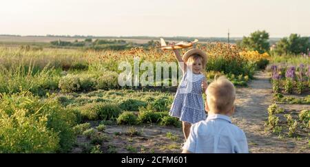 infancia, provence concepto de estilo - banner 3 años de edad rubia niña niño en vestido azul y sombrero de paja aspecto eslavo correr a lo largo del camino con juguete
