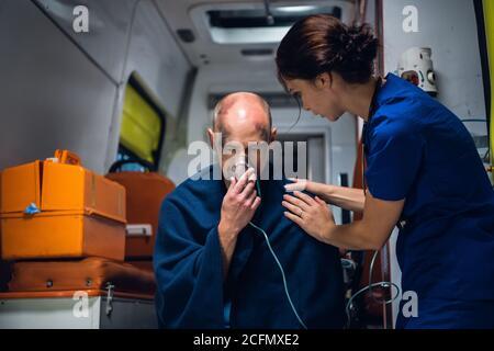 Una doctora que atiende a un paciente, que está sentada en una máscara de oxígeno en una ambulancia.