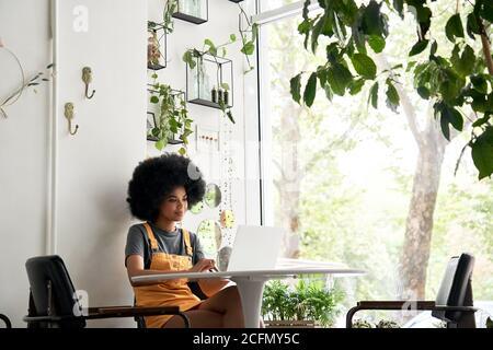 Feliz estudiante africana usando el portátil sentado en la mesa en casa, en el café.