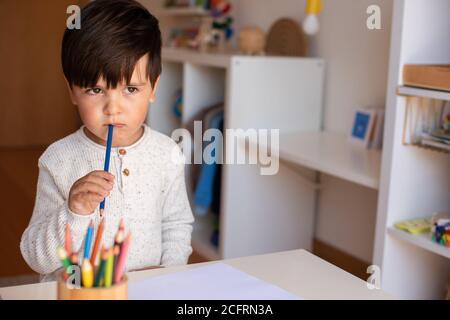 Pequeño niño de preescolar dibujo con lápices de colores. Homeschooling. Comunidad de aprendizaje. Escuela Montessori.