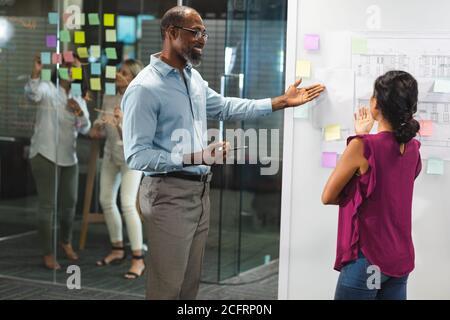 Hombre de negocios senior discutiendo con una joven empresaria sobre una pizarra blanca