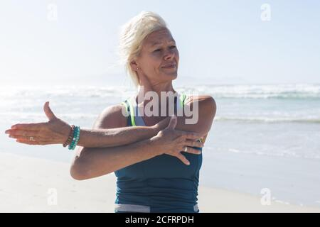 Mujer mayor haciendo ejercicio de estiramiento en la playa