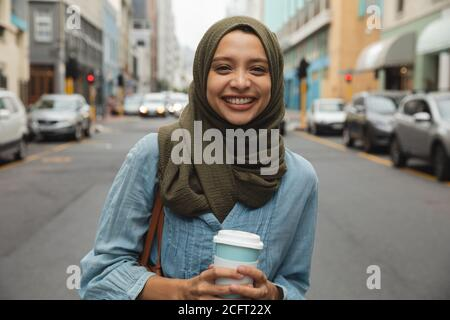 Retrato de mujer en hijab con taza de café sonriendo la calle