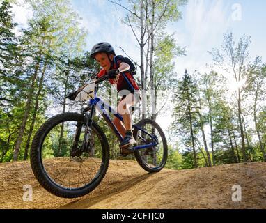 Un niño pequeño (8 años) saltando en su bicicleta de montaña