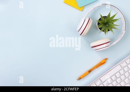 Escritorio de oficina creativo limpio moderno o mesa en la vista superior O Flat Lay y Right Frame suministros de oficina como teclado, auriculares, lápiz, Sticky Nota,plantas de oficina