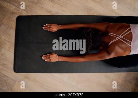 Vista en ángulo alto de la espalda femenina mientras se ejercita y se dobla adelante en casa durante el cierre