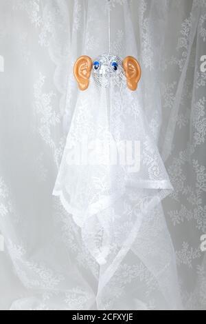 Cortina de encaje fantasma hecha con una bola disco y grandes orejas de plástico. Humor desanimado y ambiente pop. Fotografía de color mínimo