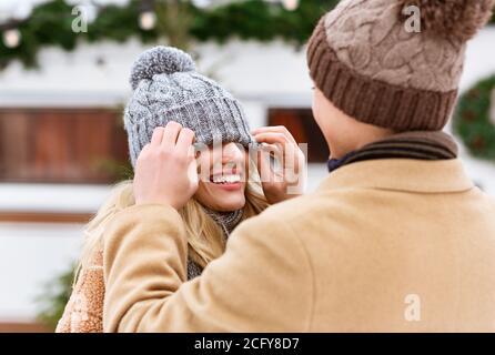 Pareja romántica divertirse al aire libre en invierno, hombre jugando con el sombrero de novia