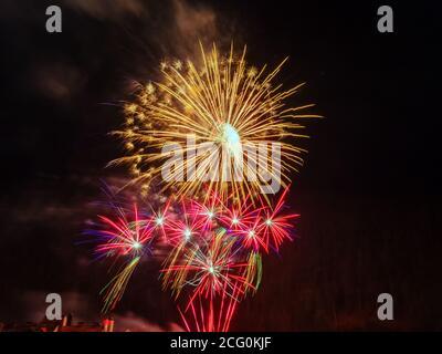 Gran flash dorado de fuegos artificiales y muchos pequeños flashes en rojo con chispas lila contra un cielo oscuro