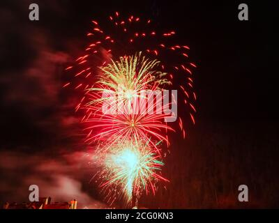 Brillos de fuegos artificiales en tonos rojos contra una oscuridad cielo