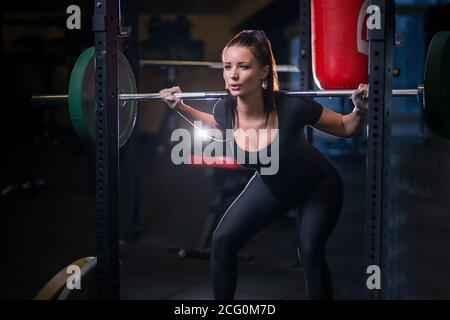 Mujer trabajando en un gimnasio haciendo flexiones. Joven que trabaja utilizando barbell con pesos pesados en un club de fitness.