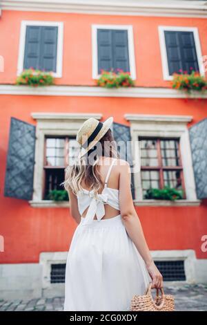 Mujer joven caminando con vestido con estilo y accesorios en la vieja ciudad de Lviv. Moderno sombrero de paja y bolso