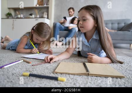 Las hermanas de los niños juegan dibujando juntos en el piso mientras los padres jóvenes se relajan en casa en el sofá, las niñas se divierten