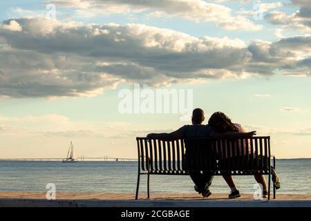 Una joven pareja afroamericana está sentada en un banco mirando al mar y al puente de Chesapeake Bay. El hombre pone su brazo sobre el hombro de la mujer