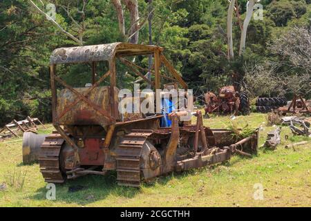 Un viejo bulldozer oxidado, abandonado en una granja con otra maquinaria