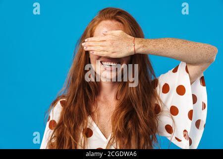 Retrato de una hermosa mujer joven alegre con pelo largo rojo con ropa de verano de pie aislado sobre fondo azul, cubre la cara