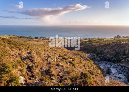 Arroyo en un valle de montaña, que fluye entre rocas con el Mar de Irlanda resaltado por la luz del sol en el fondo, Mourne Montañas, Irlanda del Norte