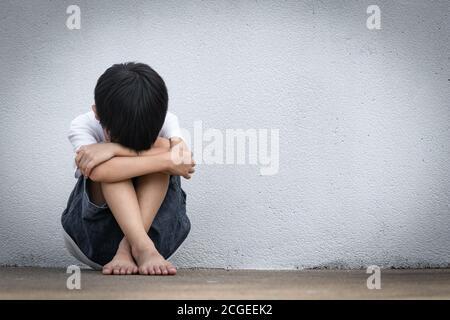Un niño sentado solo con una sensación triste. Un niño asiático cubrió su rostro con sus manos temiendo. Concepto de violencia familiar en el hogar.