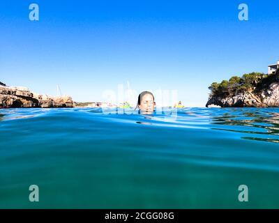 Mujer joven tomando un baño en una hermosa cala en Mallorca con solo su cabeza sobre el agua y los barcos de placer en el fondo. Concepto de vacaciones