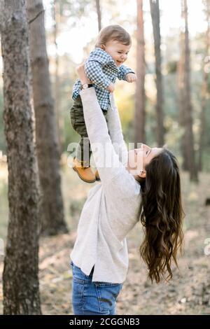 Retrato de feliz madre caucásica levantándose y jugando con su lindo hijo, disfrutando de su paseo conjunto en el bosque de pinos juntos. Feliz familia