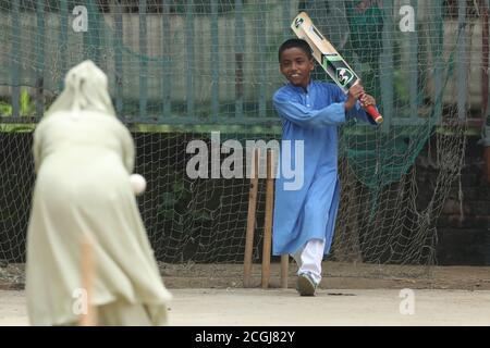 Dhaka, Bangladesh. 11 de septiembre de 2020. Jhorna Akter jugando al Cricket con su hijo Sheikh Yamin Sinan en el área de Paltan en Dhaka.las escuelas para niños aún están cerradas debido a la pandemia de Coronavirus (COVID-19) así que una madre sale a jugar al Cricket con su hijo en Dhaka, Bangladesh. Crédito: SOPA Images Limited/Alamy Live News