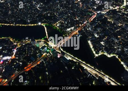 Dhaka, Bangladesh. 11 de septiembre de 2020. Vista aérea desde Drone: Ciudad nocturna volando sobre la carretera y luces nocturnas, en Dhaka, Bangladesh, 11 de septiembre de 2020. Con una densidad de 47,400 personas por kilómetro cuadrado, Dhaka siguió siendo la ciudad más densamente poblada del planeta. La población de Dhaka está aumentando cada día a medida que la gente se mueve hacia ella desde diferentes zonas del país para hacer uso de las instalaciones. La población de Dhaka en 2020 se estima ahora en 21,005,860 habitantes. En 1950, la población de Dhaka era de 335,760 habitantes. Dhaka ha crecido en 3,408,684 desde 2015, lo que representa un cambio anual del 3.60%. Estos populatio