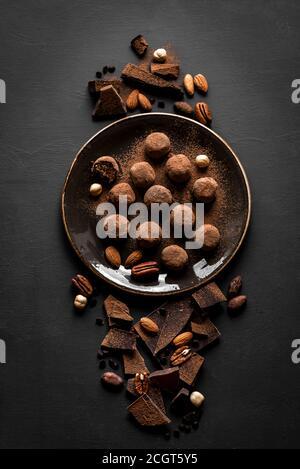 Trufas de chocolate con chocolate negro y nueces sobre fondo negro, vista superior, espacio de copia. Bolas de energía de chocolate caseras veganas o trufas para desse