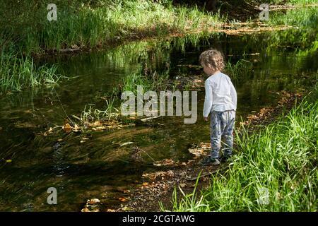 Un niño pequeño varón caucásico mirando con interés en el río Slea en Sleaford Lincolnshire desde sus orillas cerca de Cogglesford molino