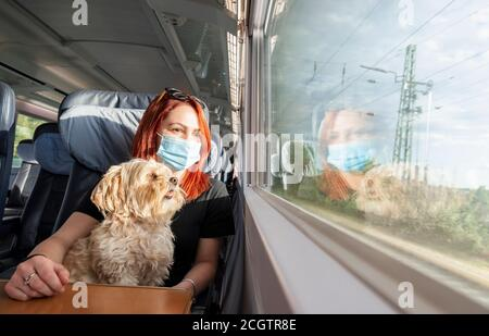 Joven pelirroja y perro viajando en tren, durante una pandemia. Niña milenaria con una máscara médica en un tren interurbano alemán, en clase de negocios.