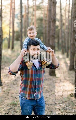 Feliz familia alegre, guapo padre barbudo y su pequeño y lindo hijo bebé en el parque de otoño, jugando y riendo. Papá con niño pequeño sentado