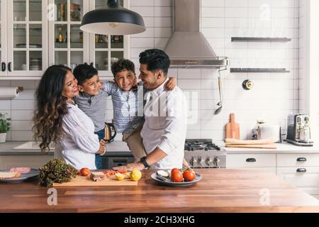 Familia abrazando y jugando unos con otros en la cocina divertida tiempo