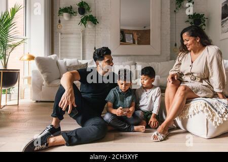 Mamá y papá riendo mientras los niños pequeños juegan teléfono en la sala de estar