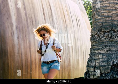 Cheerful beautiful young woman walk aoutdoor enjoying the day - concept of people in activity in the city - backpack and happy female lifestyle