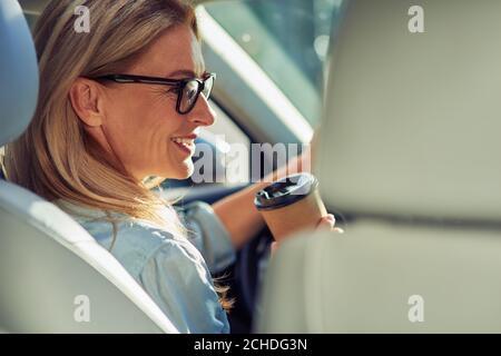 Vista trasera de una hermosa mujer de negocios de mediana edad con gafas sentada detrás del volante en un coche, bebiendo café y sonriendo