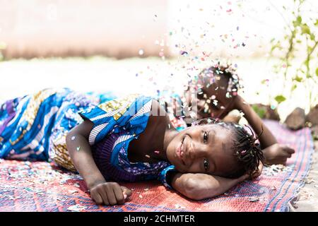 Dos preciosas niñas africanas niños Diversión con Confetti Outdoors