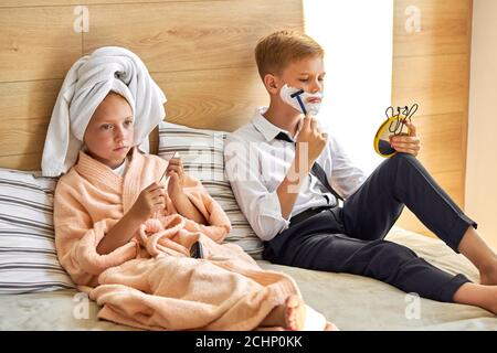 adorable pareja de niños tienen feliz mañana, cuidar de sí mismos, chico se está afeitando la barba con espuma de afeitar en la cara, en casa en la cama, chica con toalla en h.