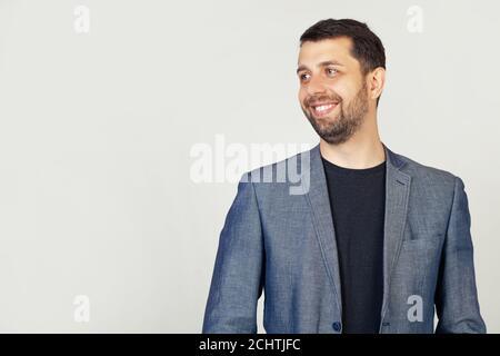 Primer plano de un guapo tipo barbudo en una chaqueta de pie en el perfil, mirando al lado, posando para una foto. Un hombre mirando al lado con una sonrisa en la cara, expresión natural.