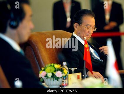 El primer Ministro de China, Wen Jiabao (R), ajusta sus auriculares mientras el primer Ministro de Japón, Naoto Kan, se sienta a su lado durante la 13ª Cumbre ASEAN Plus Three, al margen de la 17ª Cumbre ASEAN en Hanoi, el 29 de octubre de 2010. Los vínculos entre China y Japón se deterioraron el mes pasado tras la detención de un capitán de barco pesquero chino por el guardia costero japonés, después de que sus barcos chocaron cerca de islas en disputa en el Mar de China Oriental. REUTERS/Damir Sagolj (VIETNAM - Tags: POLÍTICA)