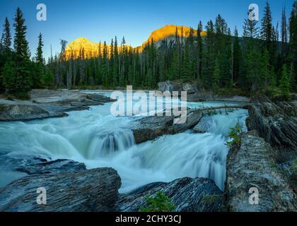 La puesta de sol sobre el río Kicking Horse fluye desde las montañas, se convirtió en una cascada antes de que pase por debajo de un puente natural, el Parque Nacional Yoho