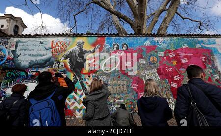 La gente observa el legendario muro John Lennon cubierto de graffiti, después de que fue repintado para conmemorar el 30 aniversario de la caída del comunismo en Praga, República Checa, el 19 de marzo de 2019. REUTERS/David W. Cerny