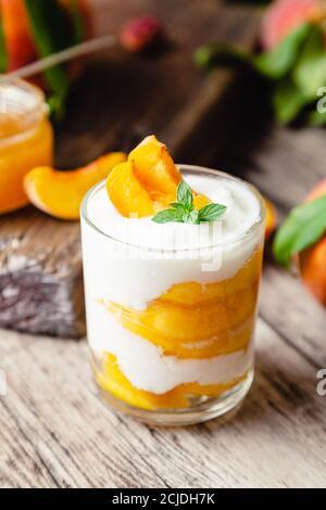 Postre de melocotón en copa de vidrio sobre mesa de madera. Postre casero con frutas. Ensalada de frutas con yogur o crema agria.