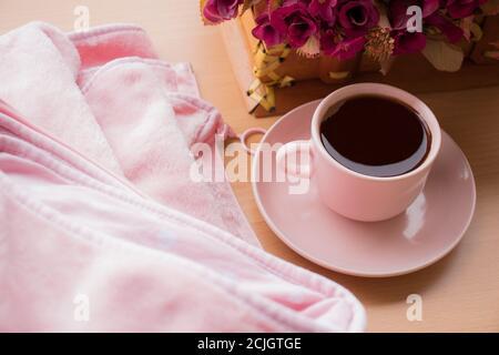 taza rosa de café negro y la flor rosa, sobre fondo de textura de madera. Concepto de plano, vista superior, café por la mañana. Día Internacional del Café.