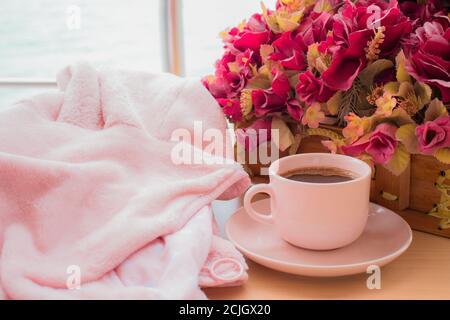 taza rosa de café negro y la flor rosa, sobre la textura de madera y el fondo del paisaje marino. relajante y concepto de café. Día Internacional del Café