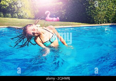 Linda chica bailando agita el cabello y la cabeza sonriendo de pie la piscina en el jardín Foto de stock