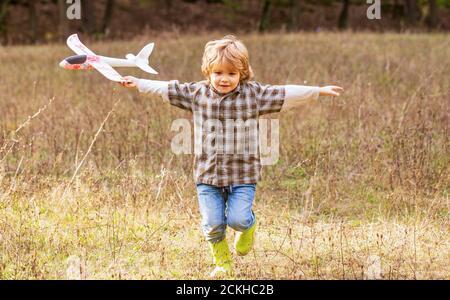 Niño pequeño con avión. Un niño sueña con ser piloto. Niño jugando con un avión de juguete. Niño feliz jugando Foto de stock